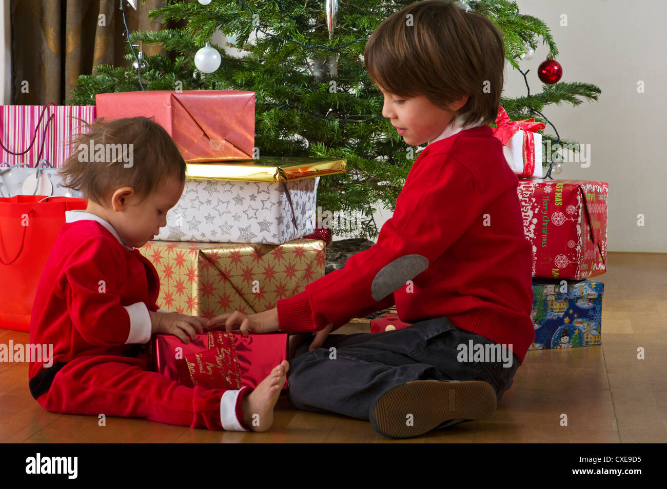 young brother and sister opening christmas gift together stock photo