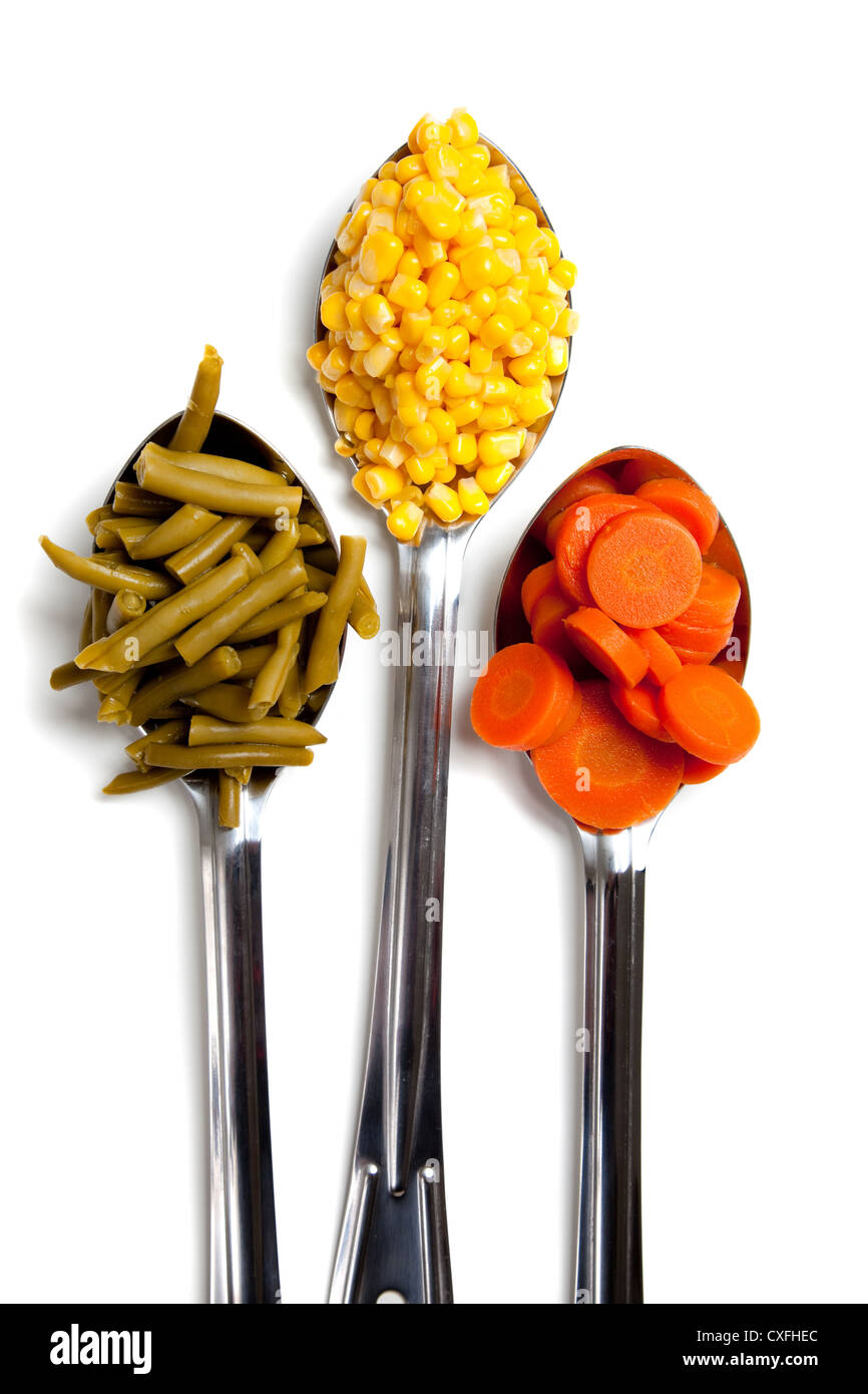 Silver commercial silver spoons with carrots, corn and green beans on a white background Stock Photo