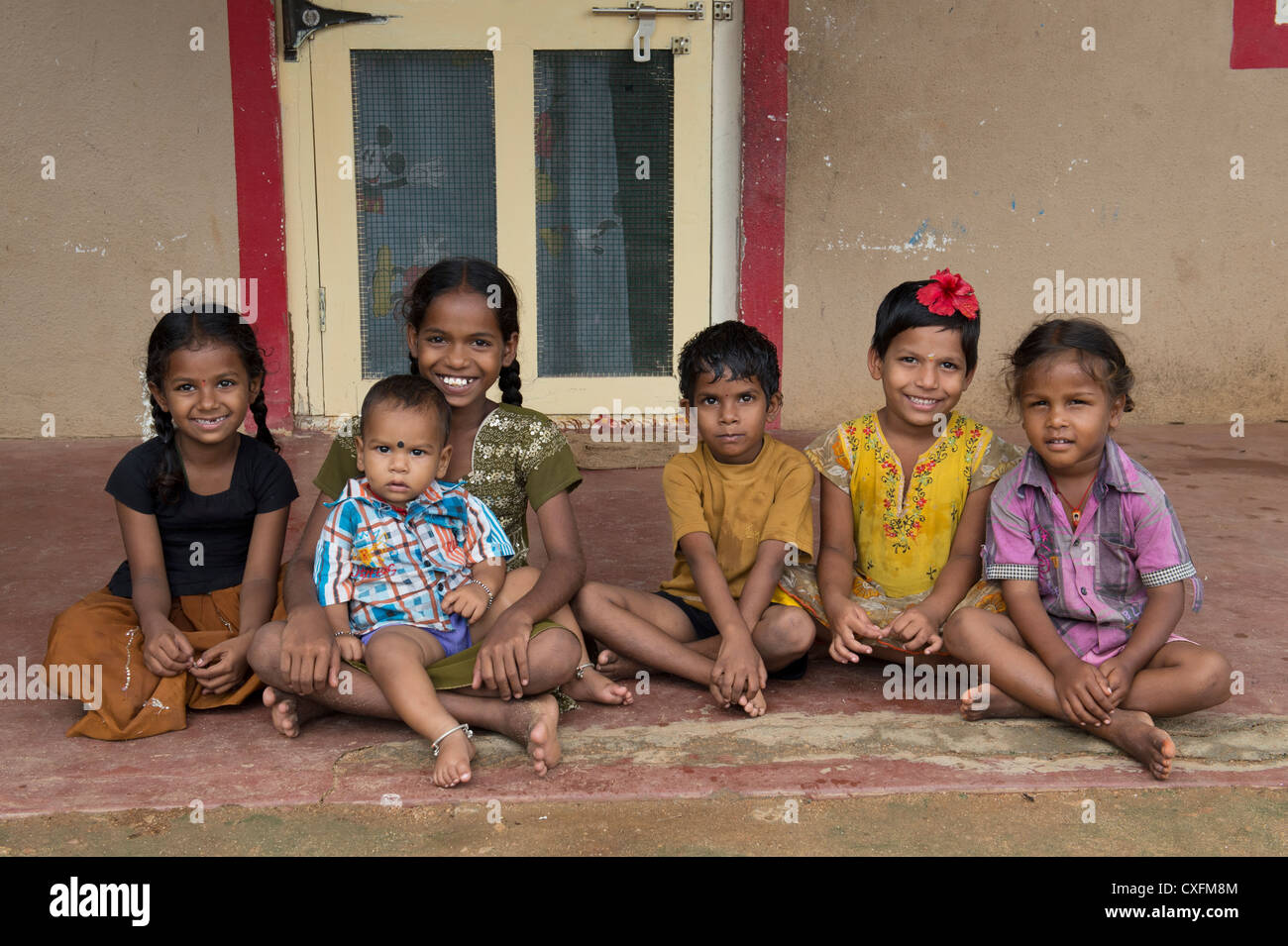 Happy young rural Indian village children sitting in front of a house smiling. Andhra Pradesh, India - Stock Image
