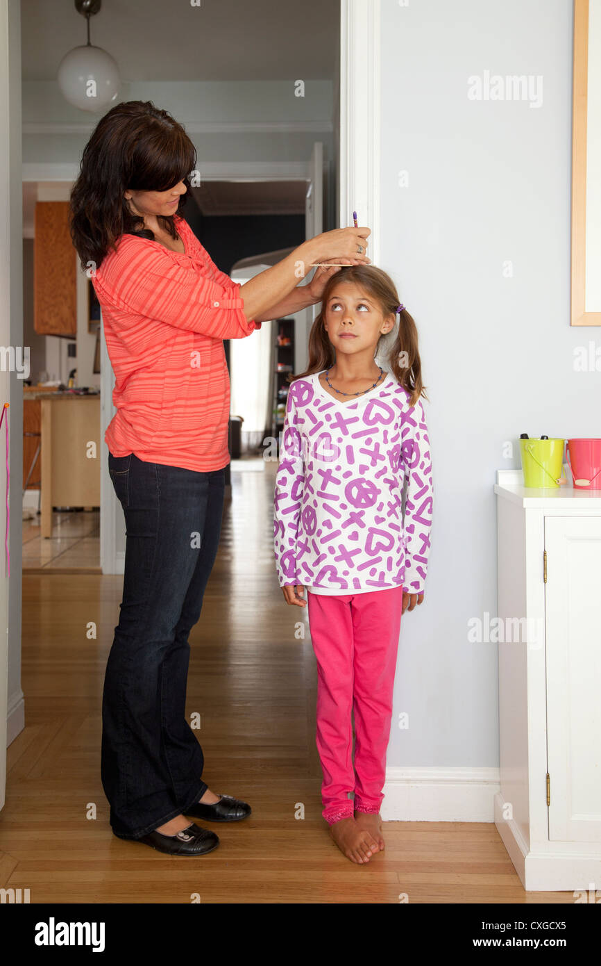 A mother is measuring her daughter's height against a wall. - Stock Image