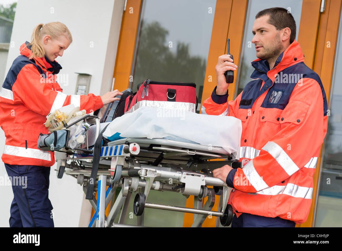 Emergency paramedics radio call ambulance house door visit doctor - Stock Image