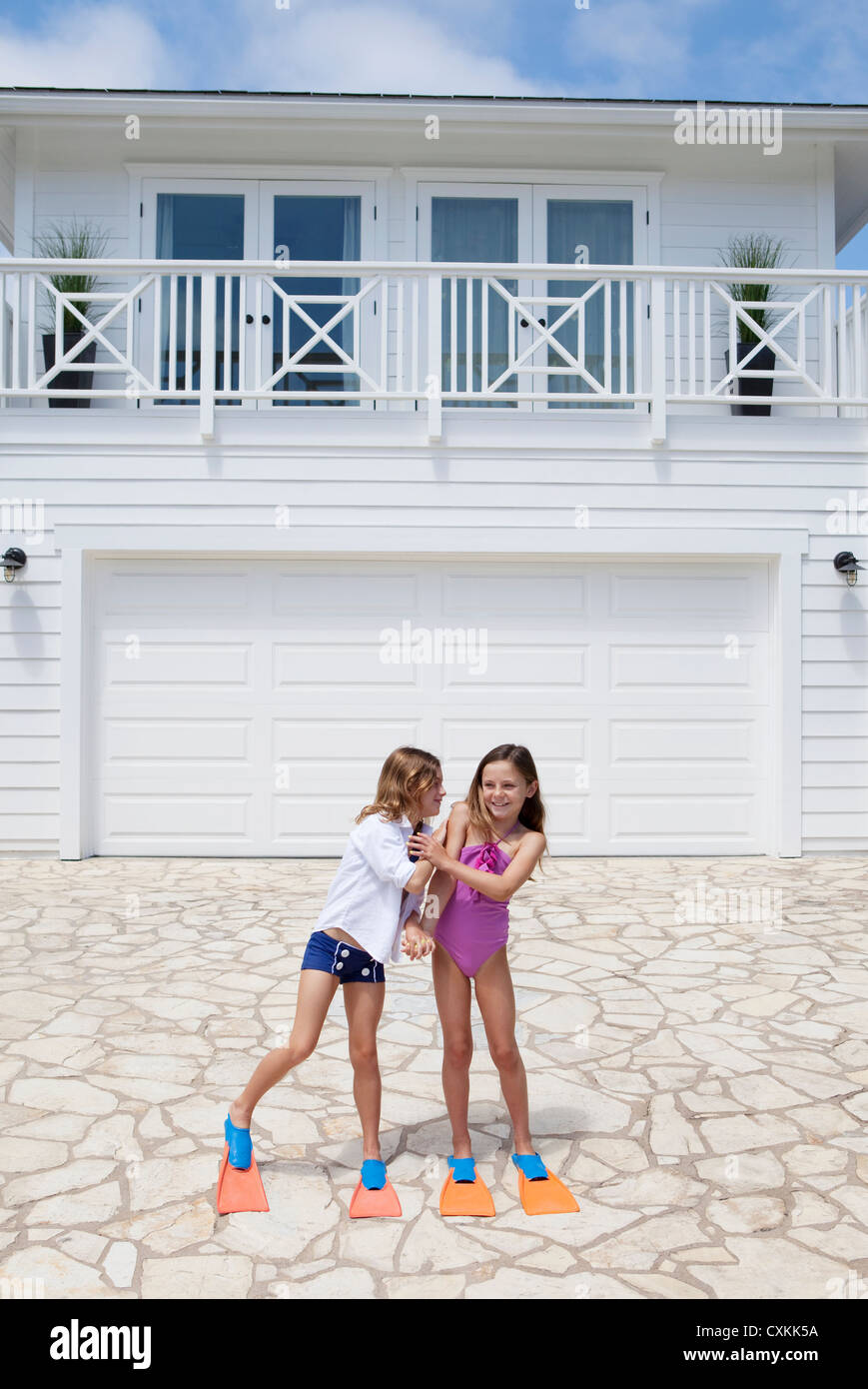 Girls in flippers in front of house - Stock Image