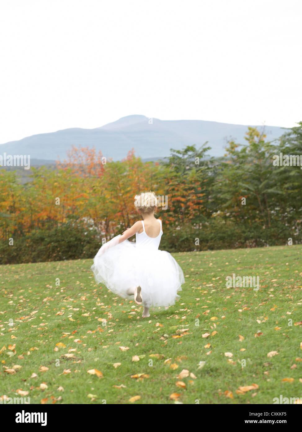 girl running in ballet costume in field - Stock Image