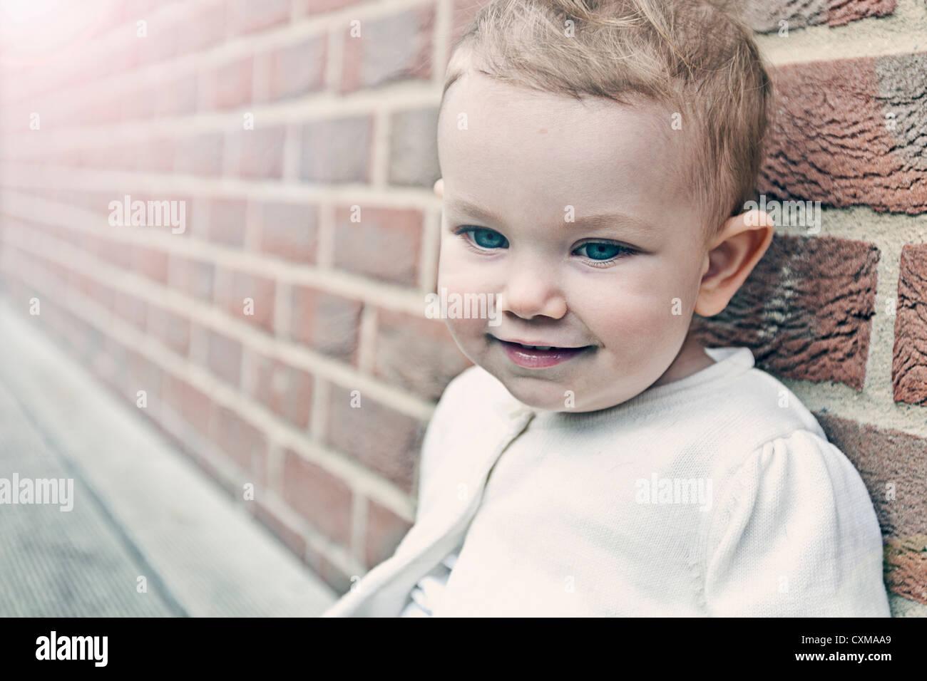 Beautiful Baby Girl against Brick Wall - Stock Image