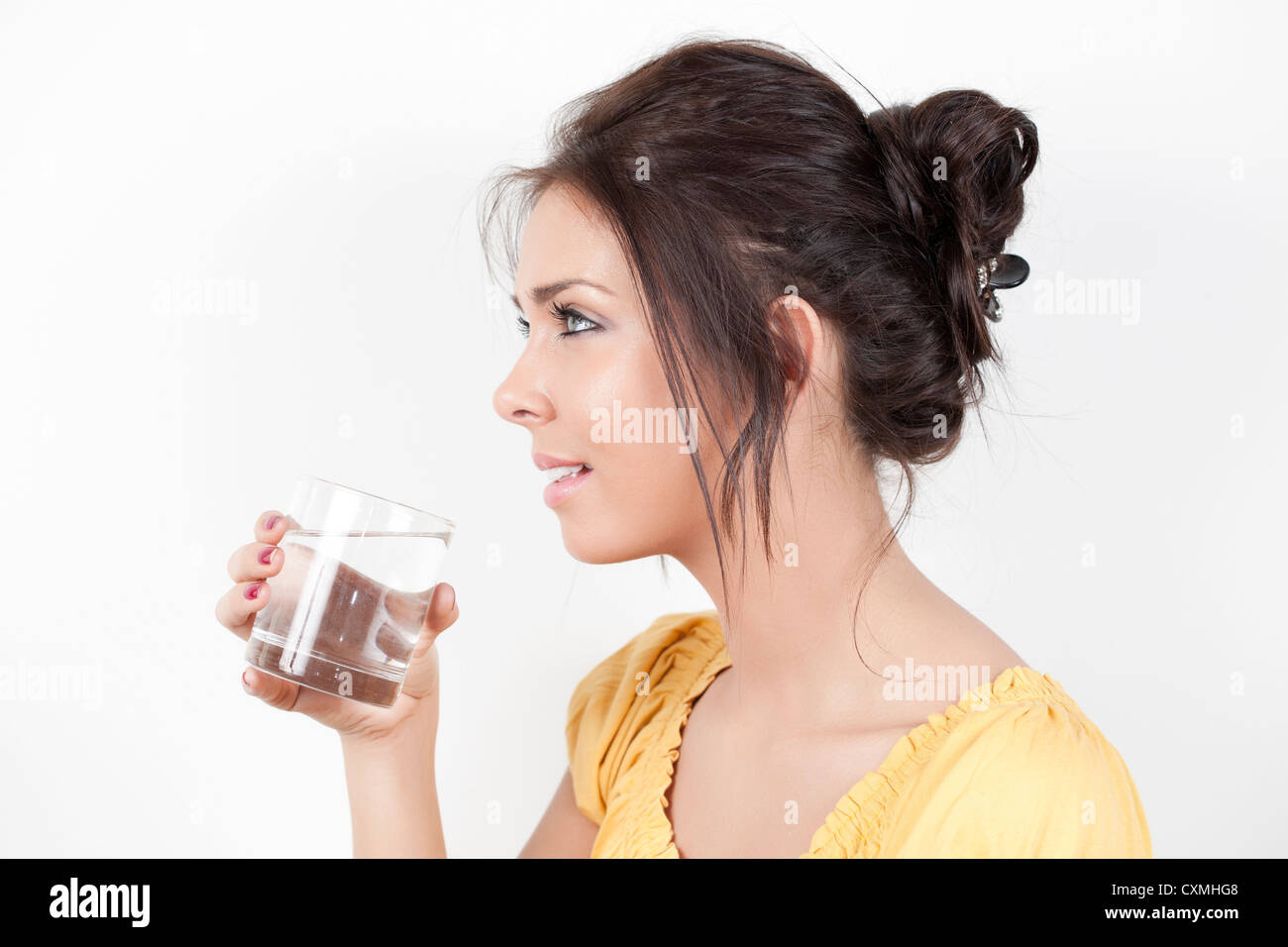 Woman drinking water from a glass - Stock Image