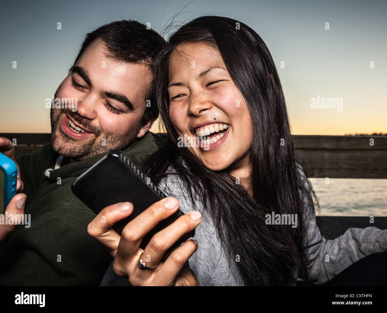 Couple using cell phones outdoors - Stock Image