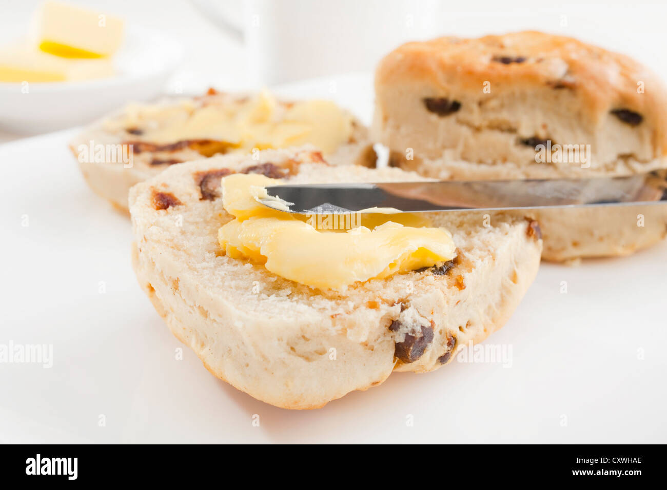 Two date scones on a white plate with butter. - Stock Image