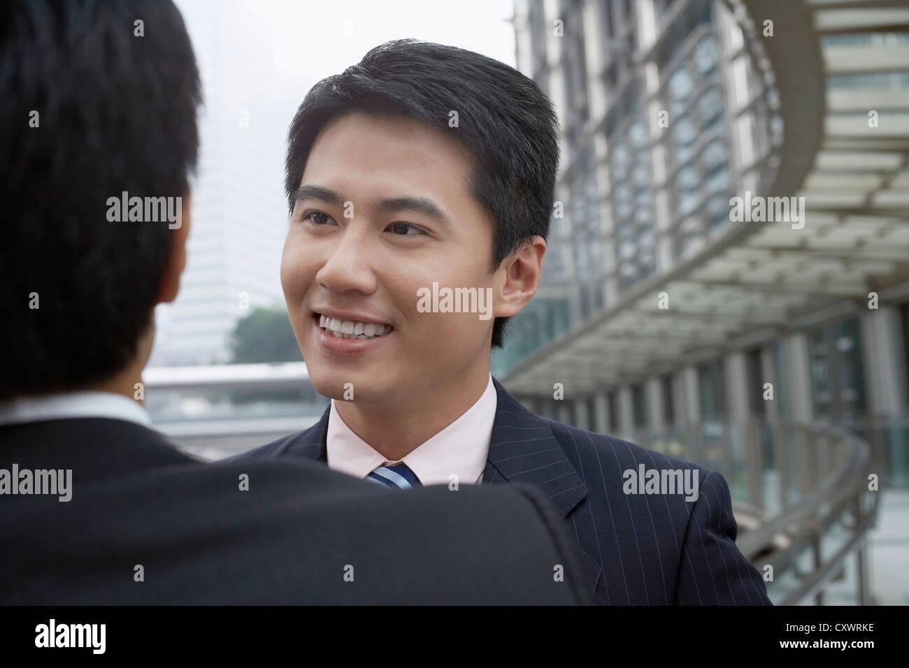 Businessmen talking on walkway - Stock Image