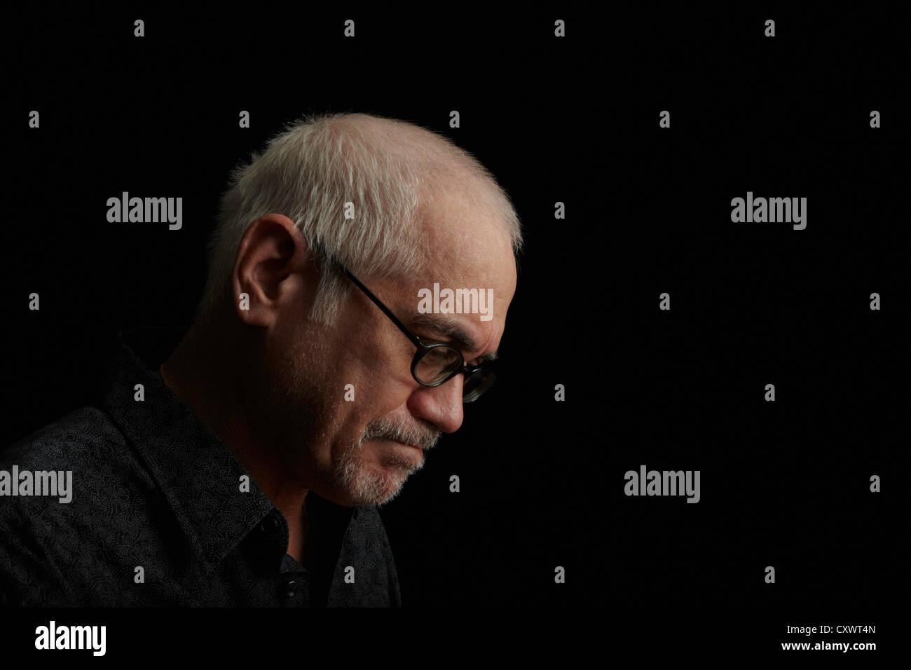Frowning older man wearing eyeglasses - Stock Image