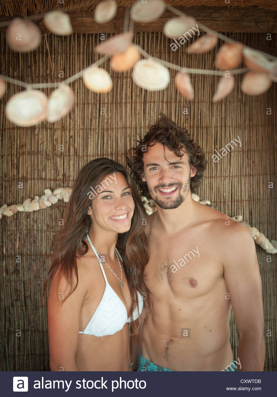 Smiling couple standing in tropical hut - Stock Image