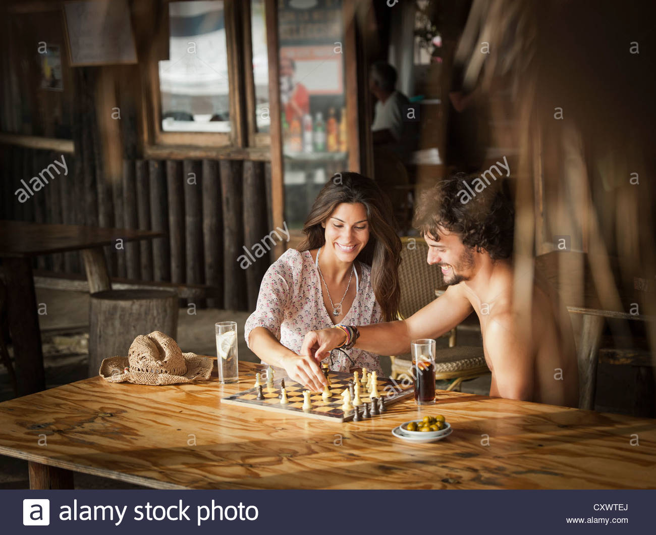 Couple playing chess in bar - Stock Image