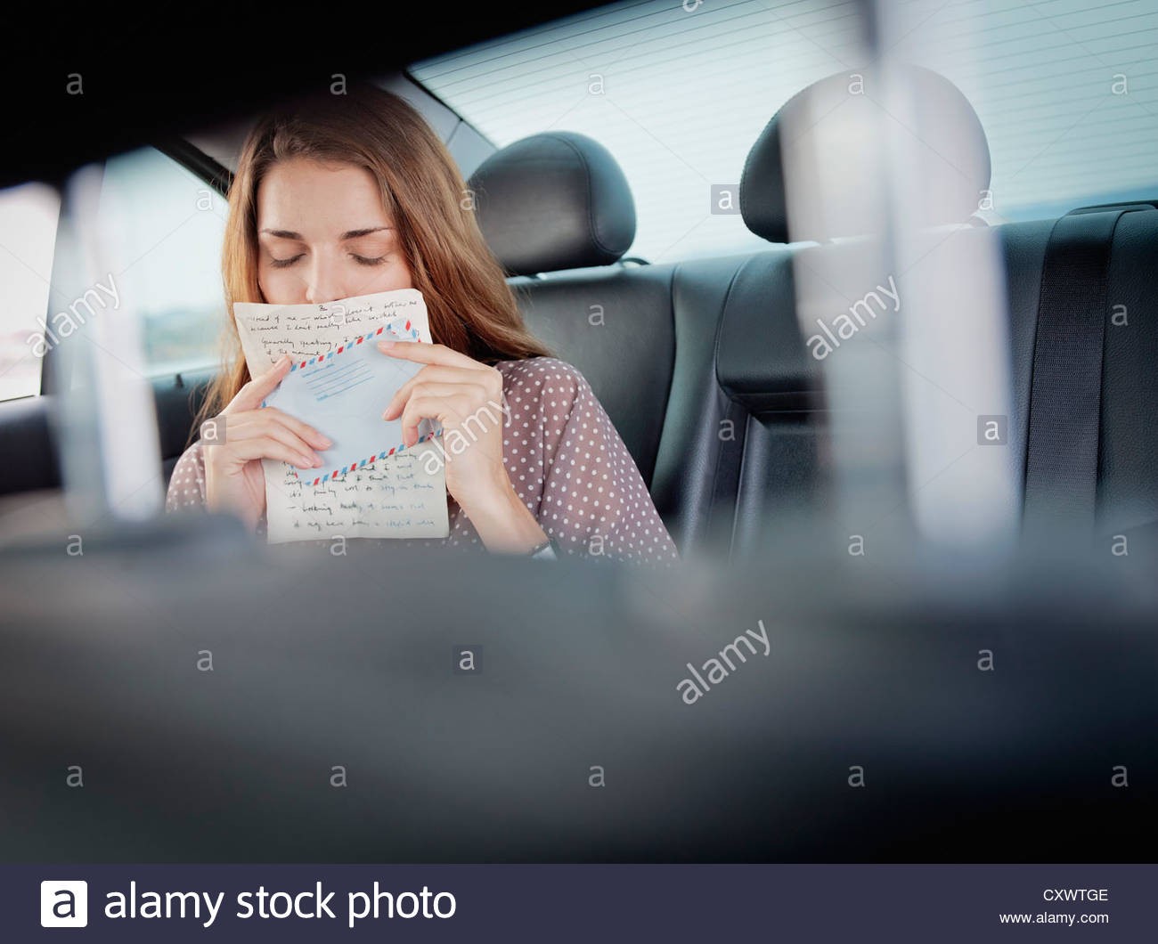 Woman kissing letter in backseat of car - Stock Image