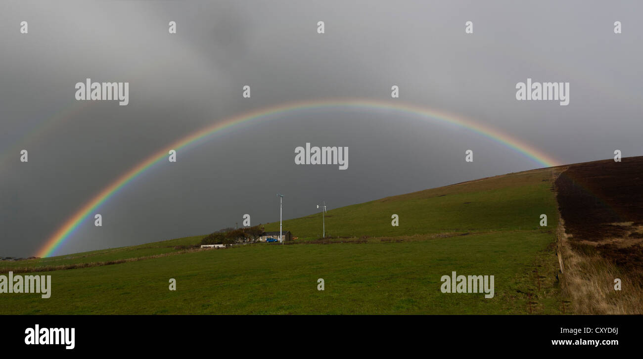 Rainbow over cottage with 2 wind turbines - Stock Image