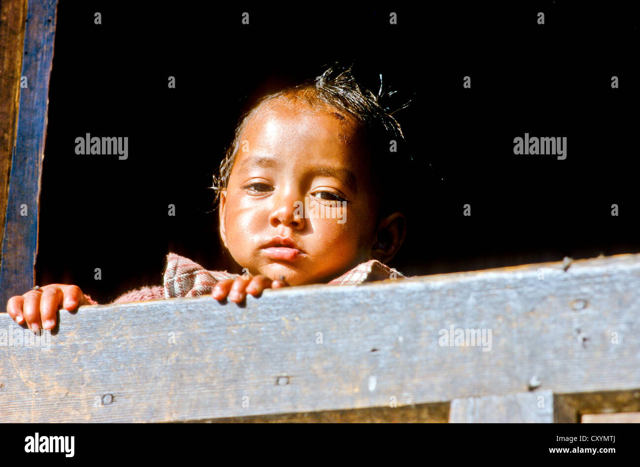 Little boy curiously looking out of a window in the small village of Gangi, India, Asia - Stock Image