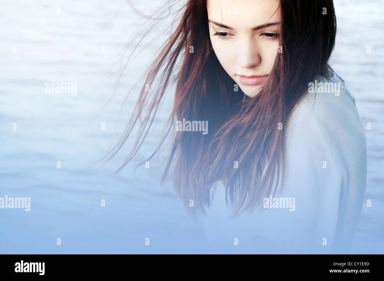 Close up of young woman with long red hair looking down beside water - Stock Image