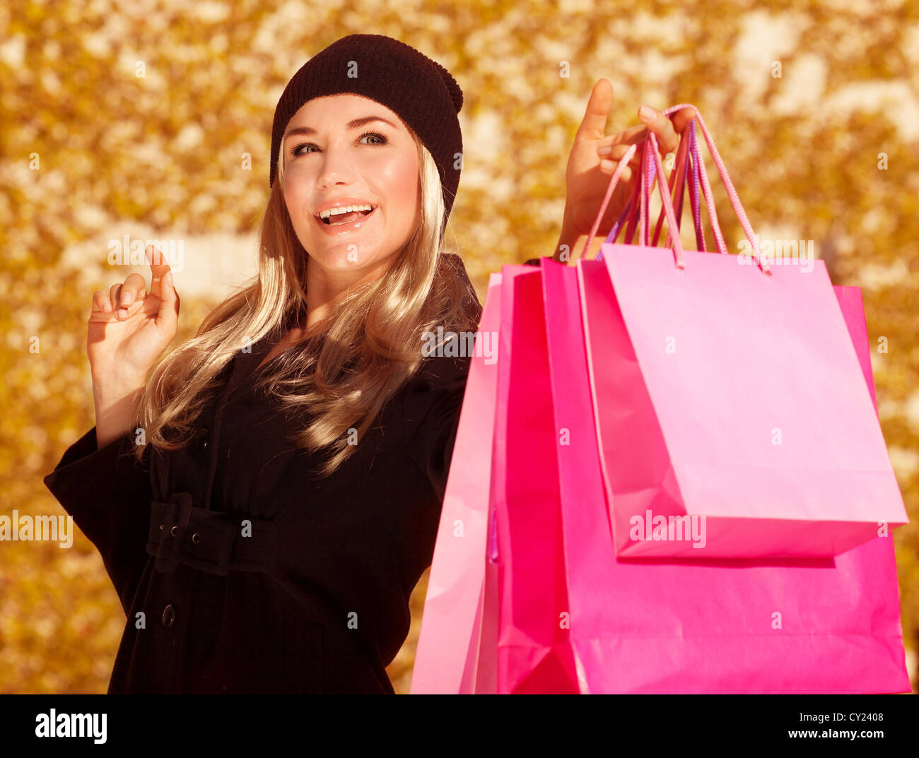 Picture of shopper girl holding presents bags in hand, beautiful customer enjoy autumnal season sales, closeup portrait - Stock Image