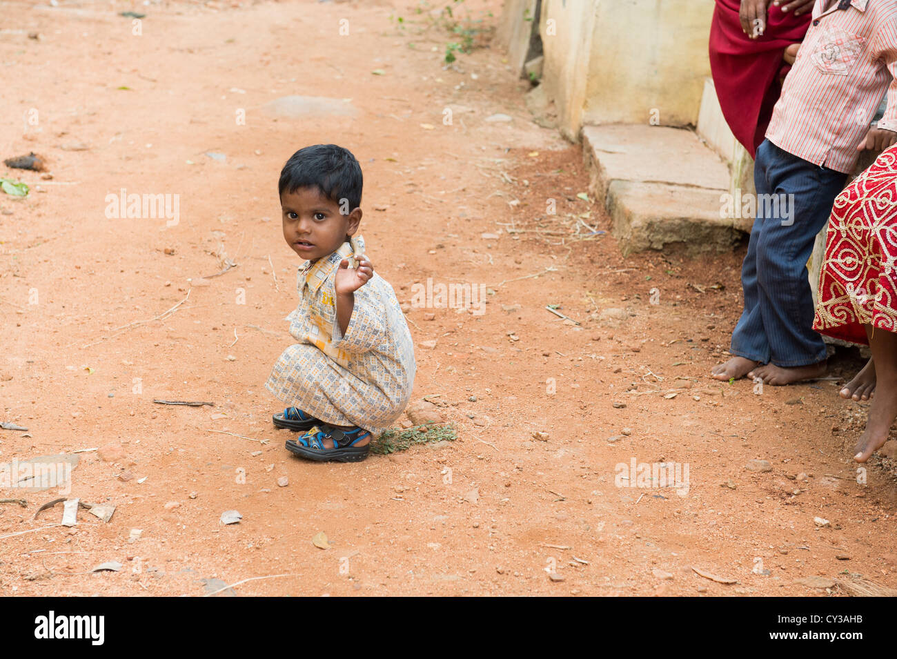 Small indian boy playing with a stick in a rural indian village. Andhra Pradesh, India - Stock Image