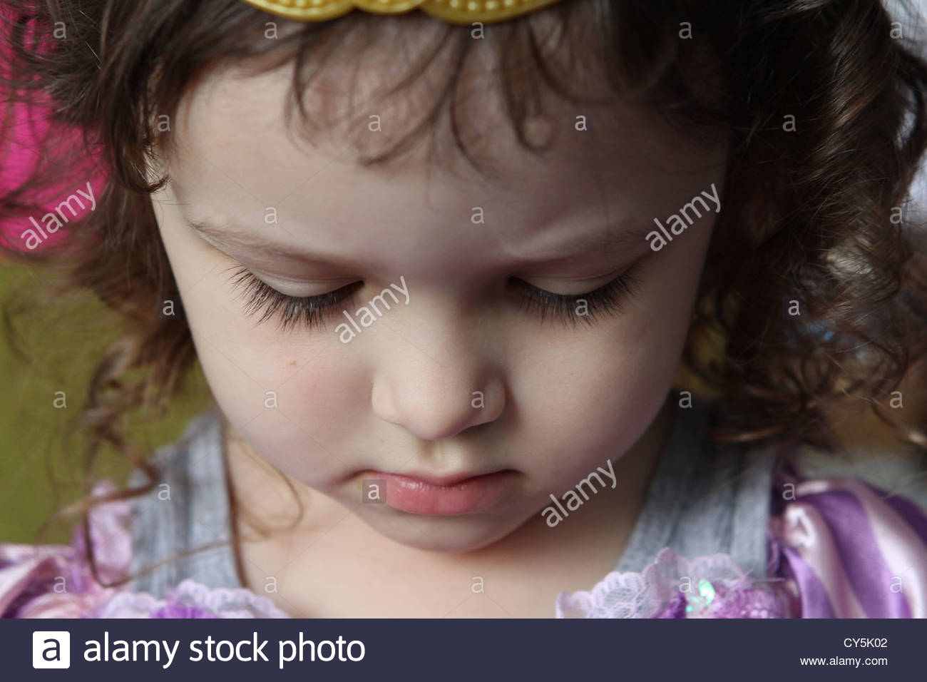 A close up of the face of a 4 year old girl with downcast eyes. - Stock Image