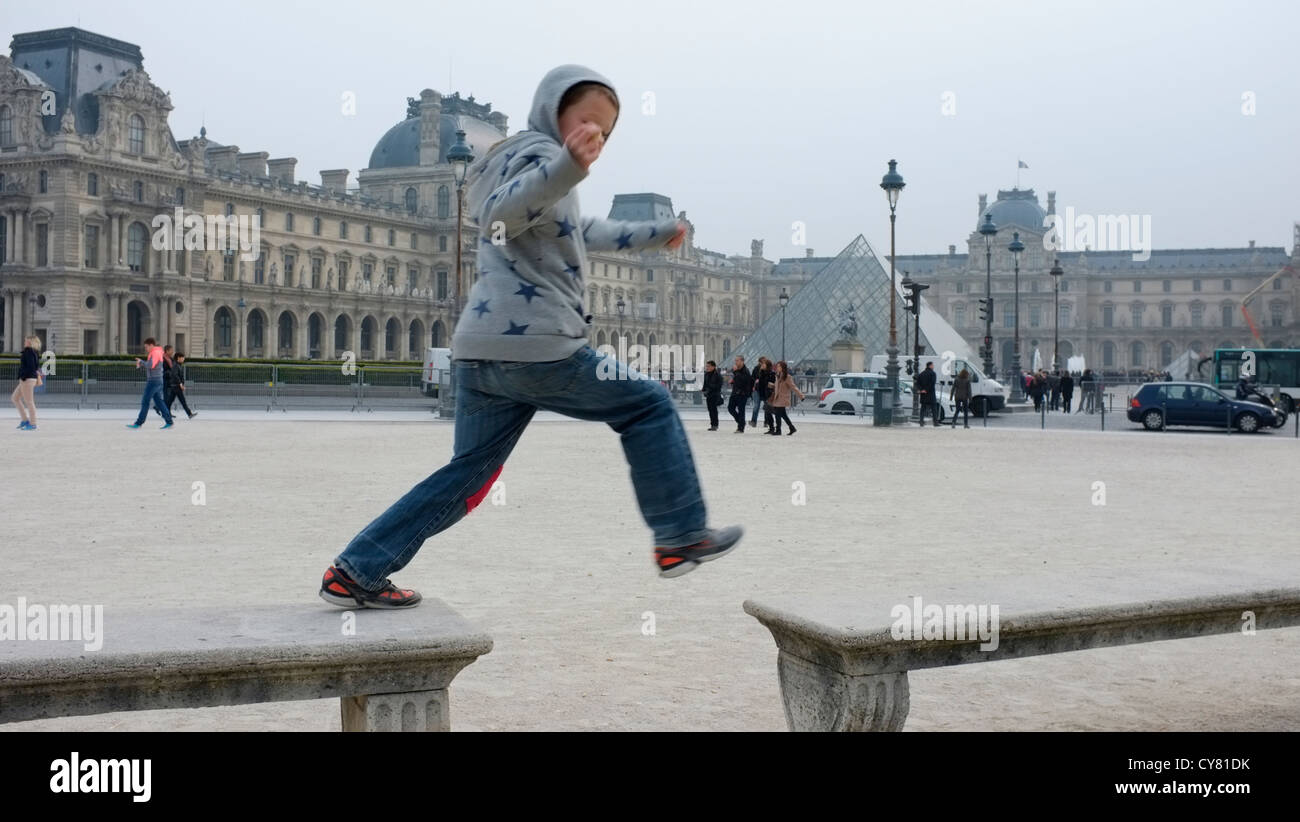 Boy jumping benches in the Jardin du Carrousel sous la neige near the Louvre Museum in Paris, France. - Stock Image