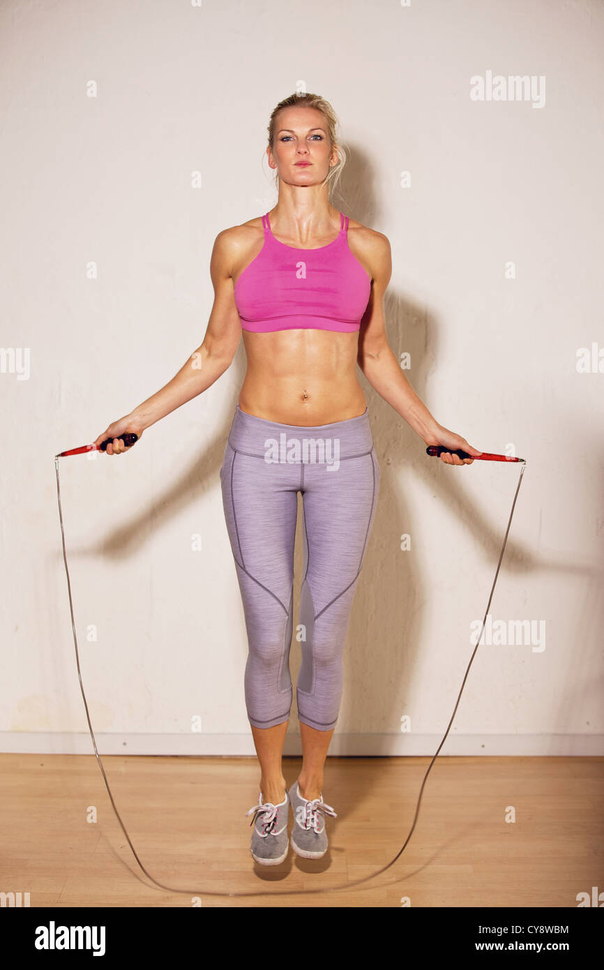 Female athlete using jump rope as her strength training - Stock Image