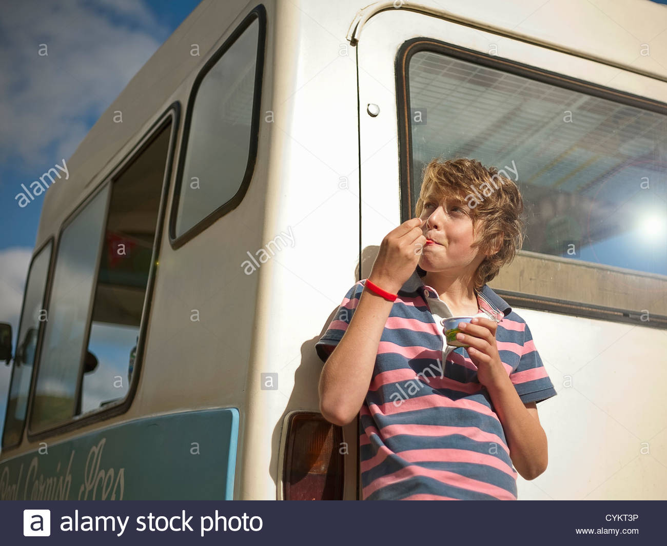Boy eating ice cream by truck - Stock Image