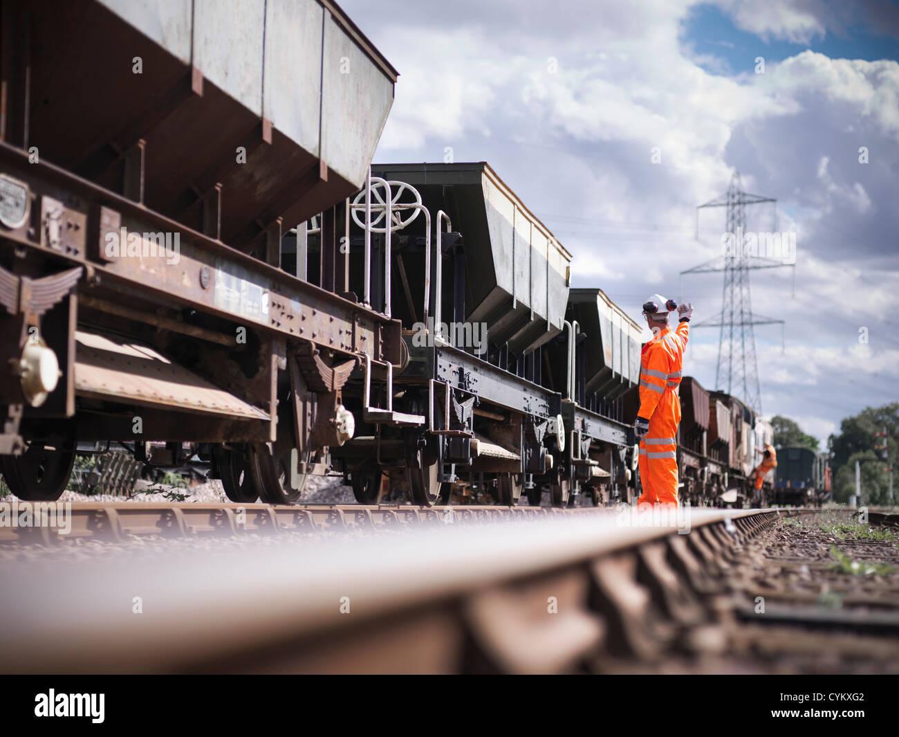 Railway workers signaling train - Stock Image