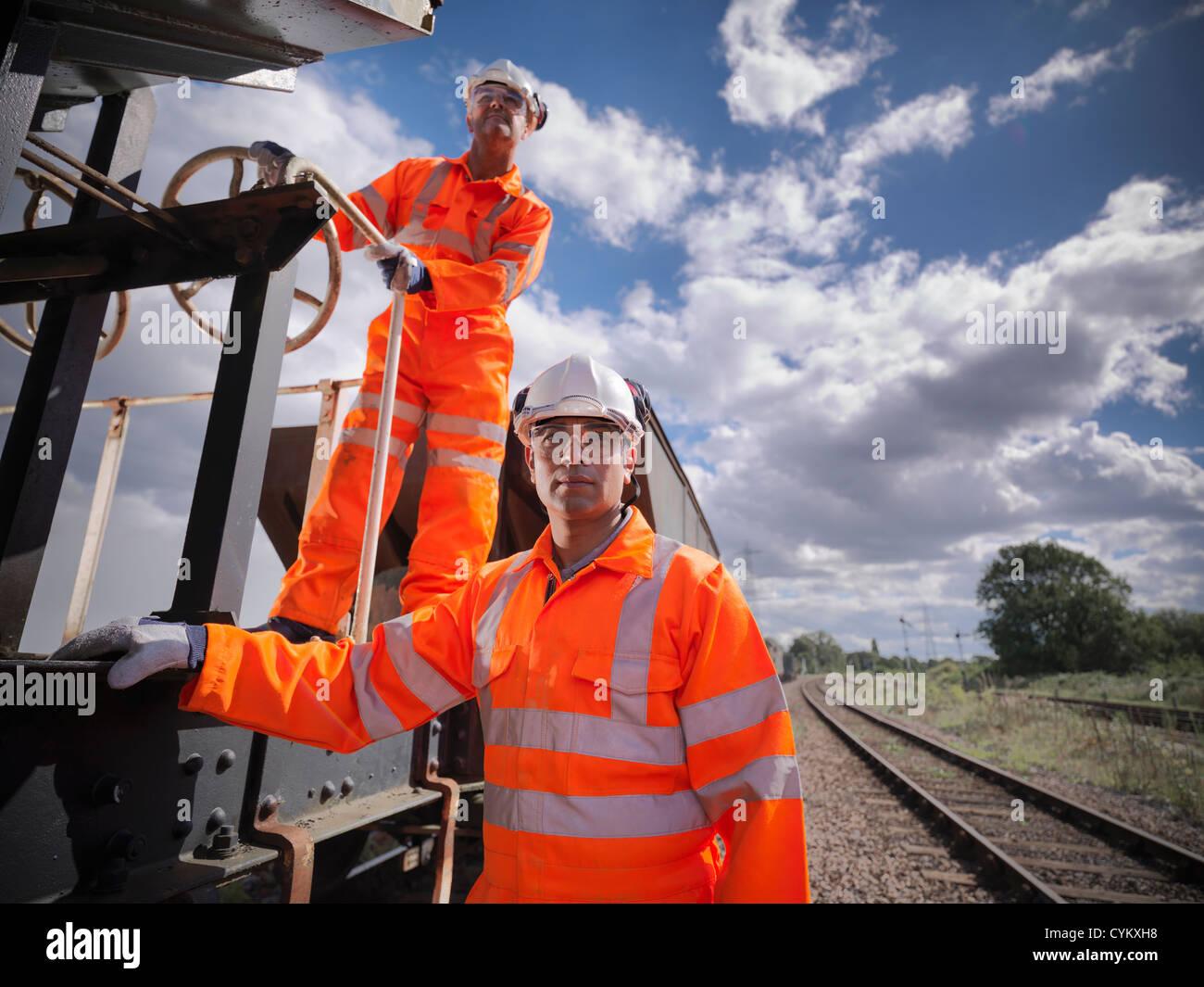 Railway workers standing on train - Stock Image