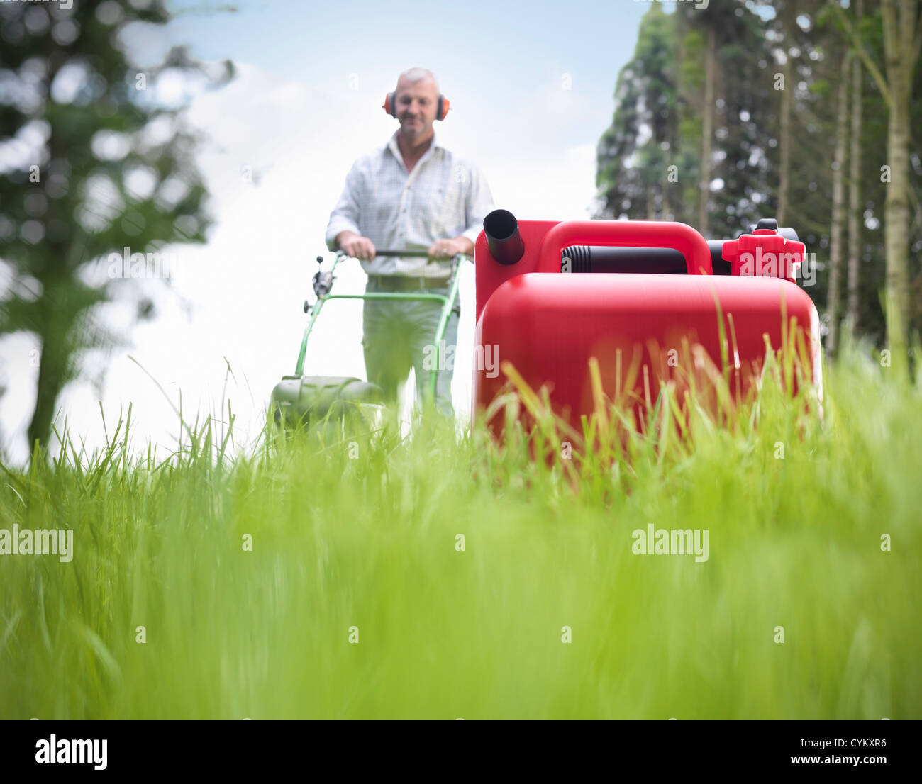 Can of gasoline on grassy lawn - Stock Image