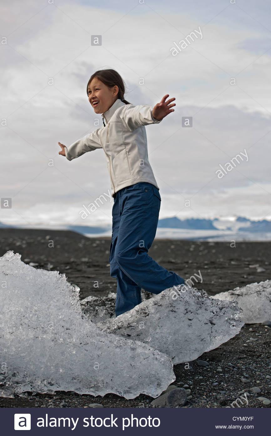 Girl balancing on glaciers - Stock Image