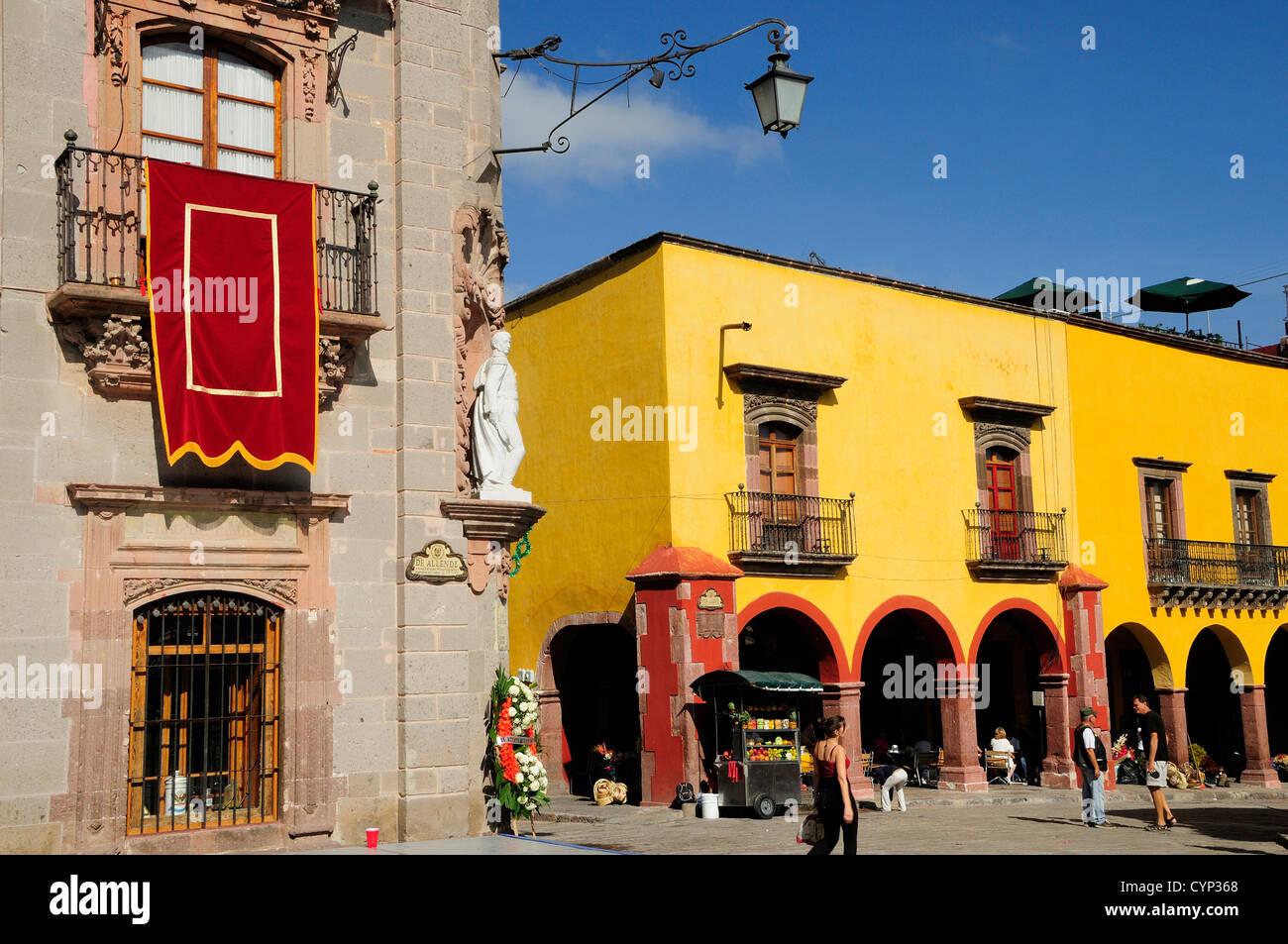 El Jardin Part view of Museo Casa de Allende and yellow painted arcades people and fruit juice vendor   Hispanic - Stock Image