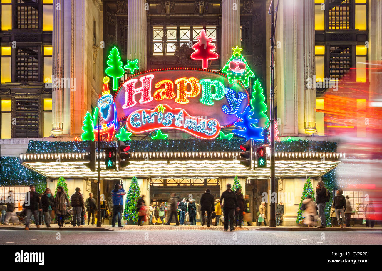 London UK. Christmas shoppers Xmas shopping at Selfridge's store Oxford Street with large neon sign lights Happy - Stock Image