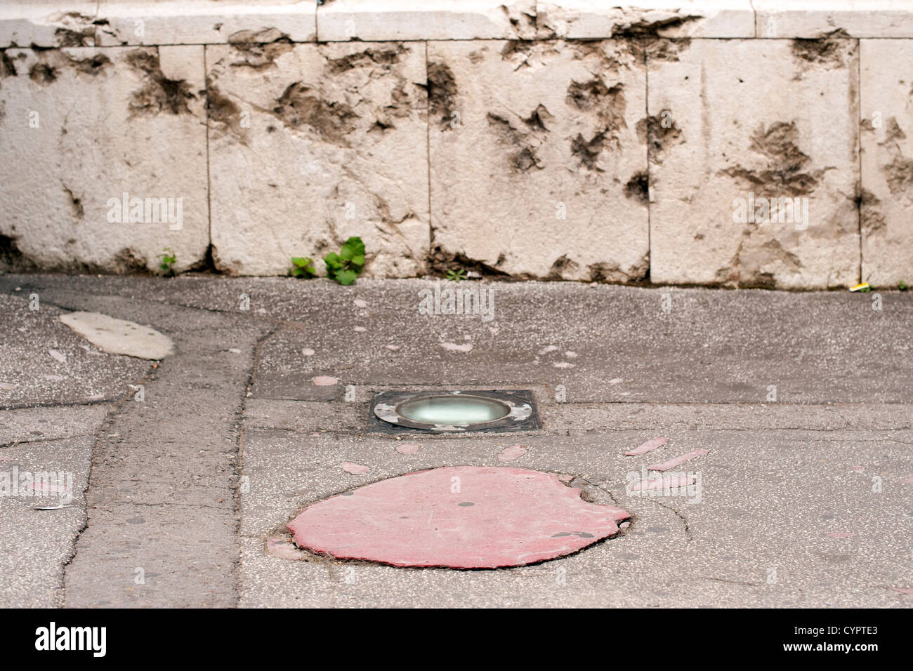 A 'Sarajevo Rose', a concrete scar caused by a mortar shell's explosion in the siege of Sarajevo during - Stock Image