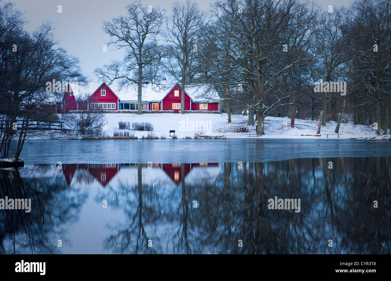 Red home a dawn near a lake with its reflection. - Stock Image