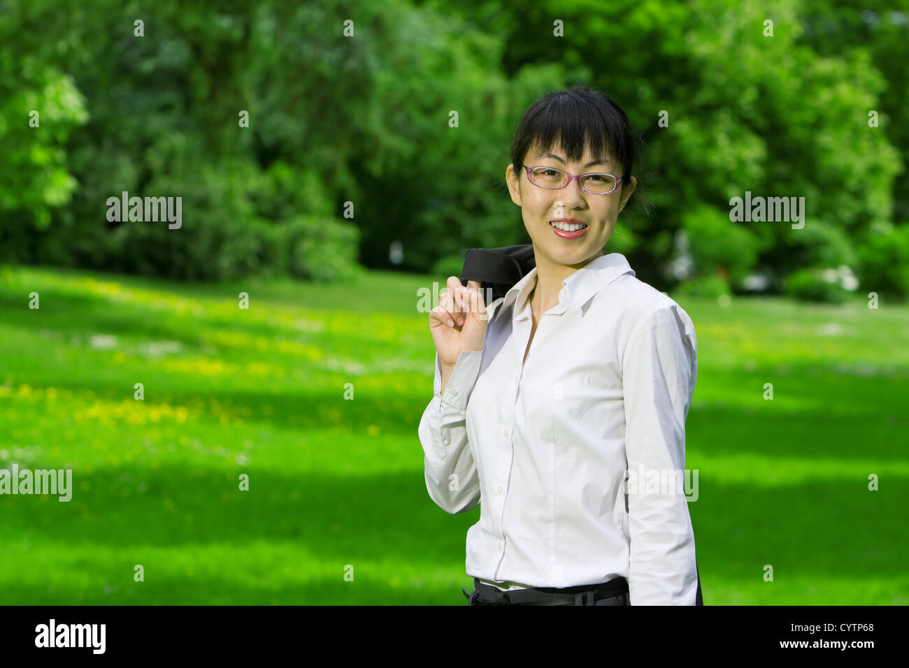 Environmentally friendly asian business woman outdoors in nature with green grass - Stock Image