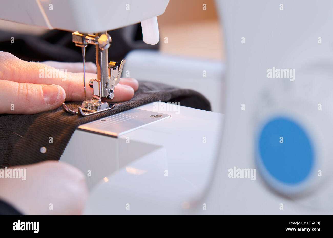 woman hands sewing on the stitching machine - Stock Image
