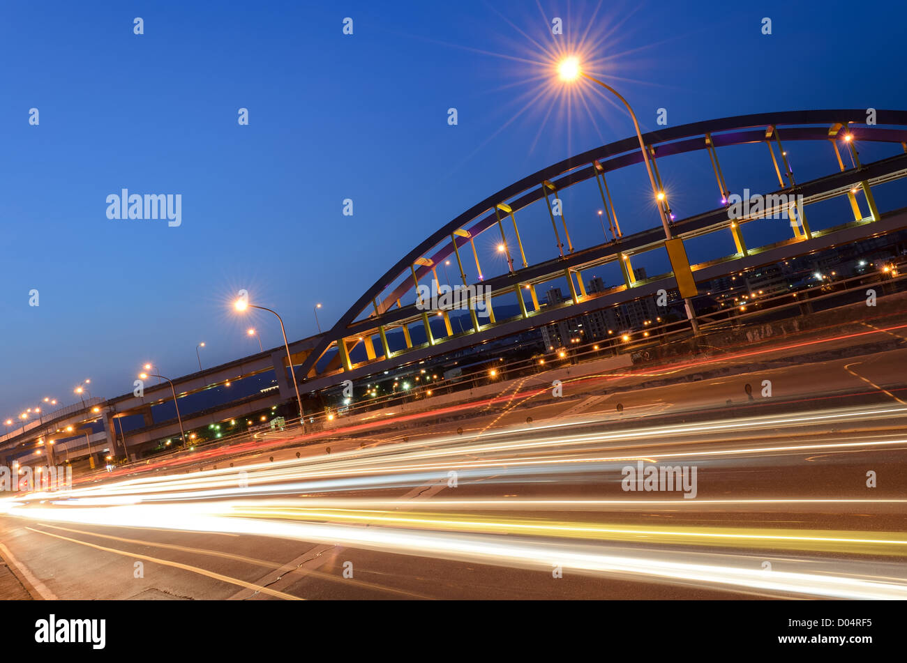 Urban transport scenery with abstract cars light in night in modem city. - Stock Image