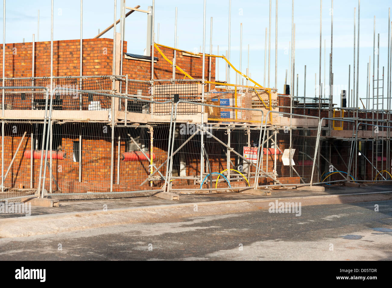 Building site for a new housing estate, UK. Scaffolding around a new house build. Stock Photo