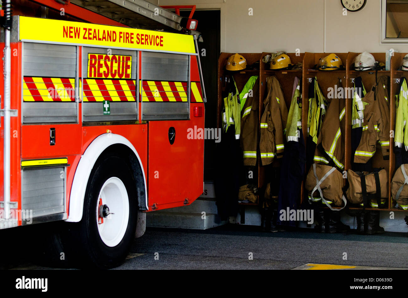 Helmets, boots and jackets in a fire station ready to be used by firefighters. - Stock Image