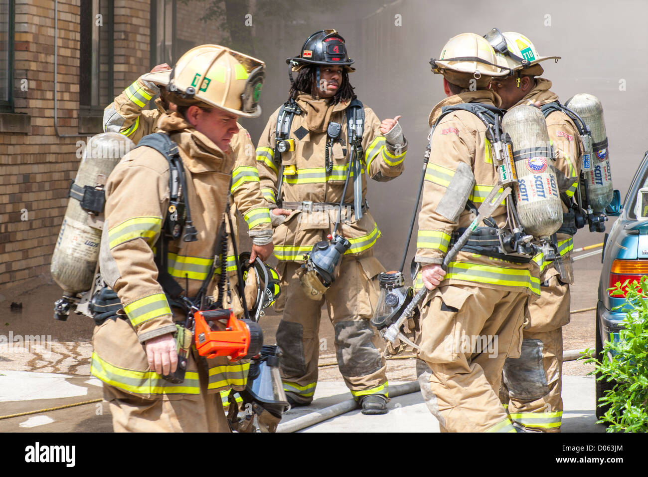 American fire fighters firemen in front of a burning building, discussing tactics. Diverse crew Caucasian, African Stock Photo