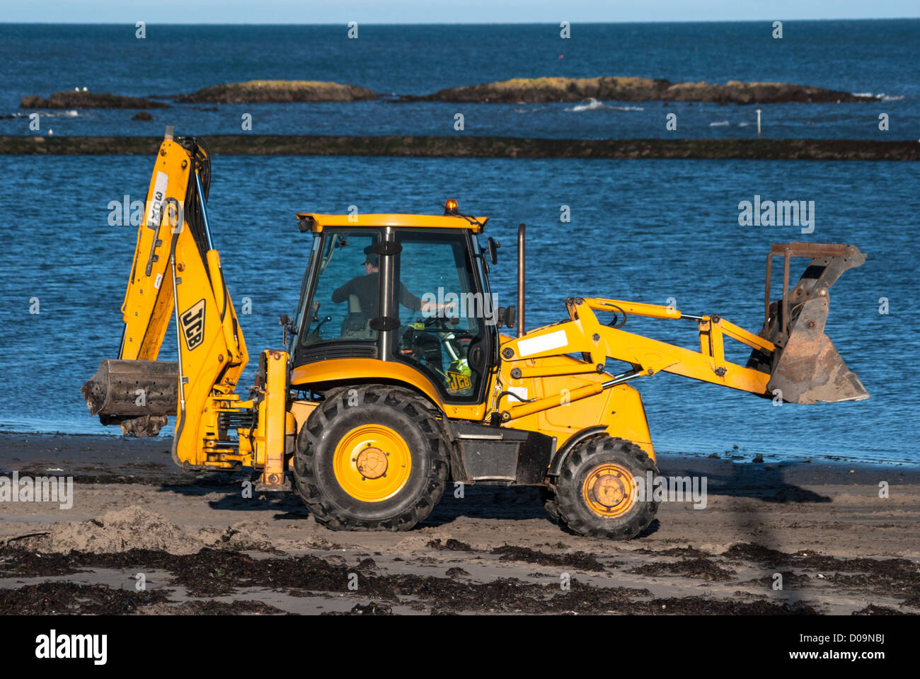 JCB at work on Millisle Beach Stock Photo
