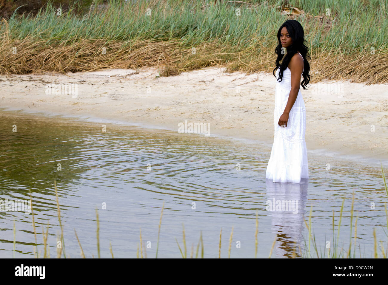 Lonely African American woman stands downcast in shallow water with a sad pensive look on her face. - Stock Image