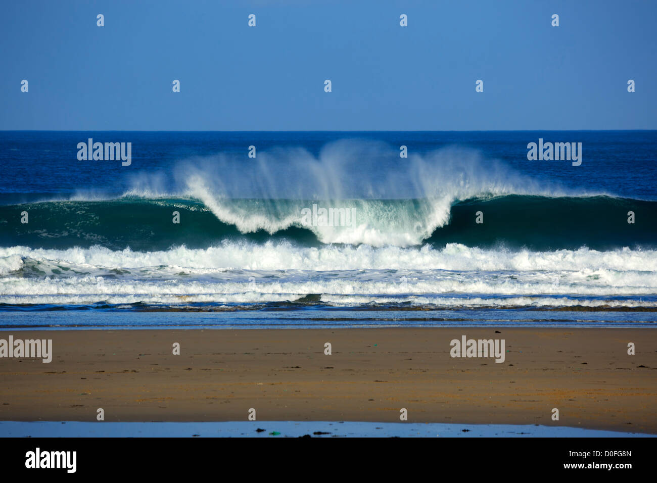 Portreath, Cornwall. A wave breaks on the beach. - Stock Image