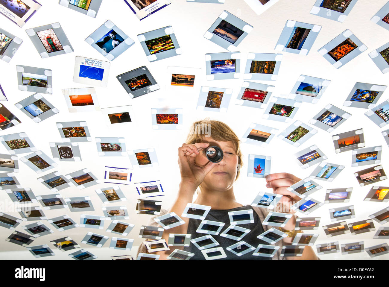 Woman, photo editor,  is looking at slides, photos, at a light table. Picture editing. Analog photography. - Stock Image