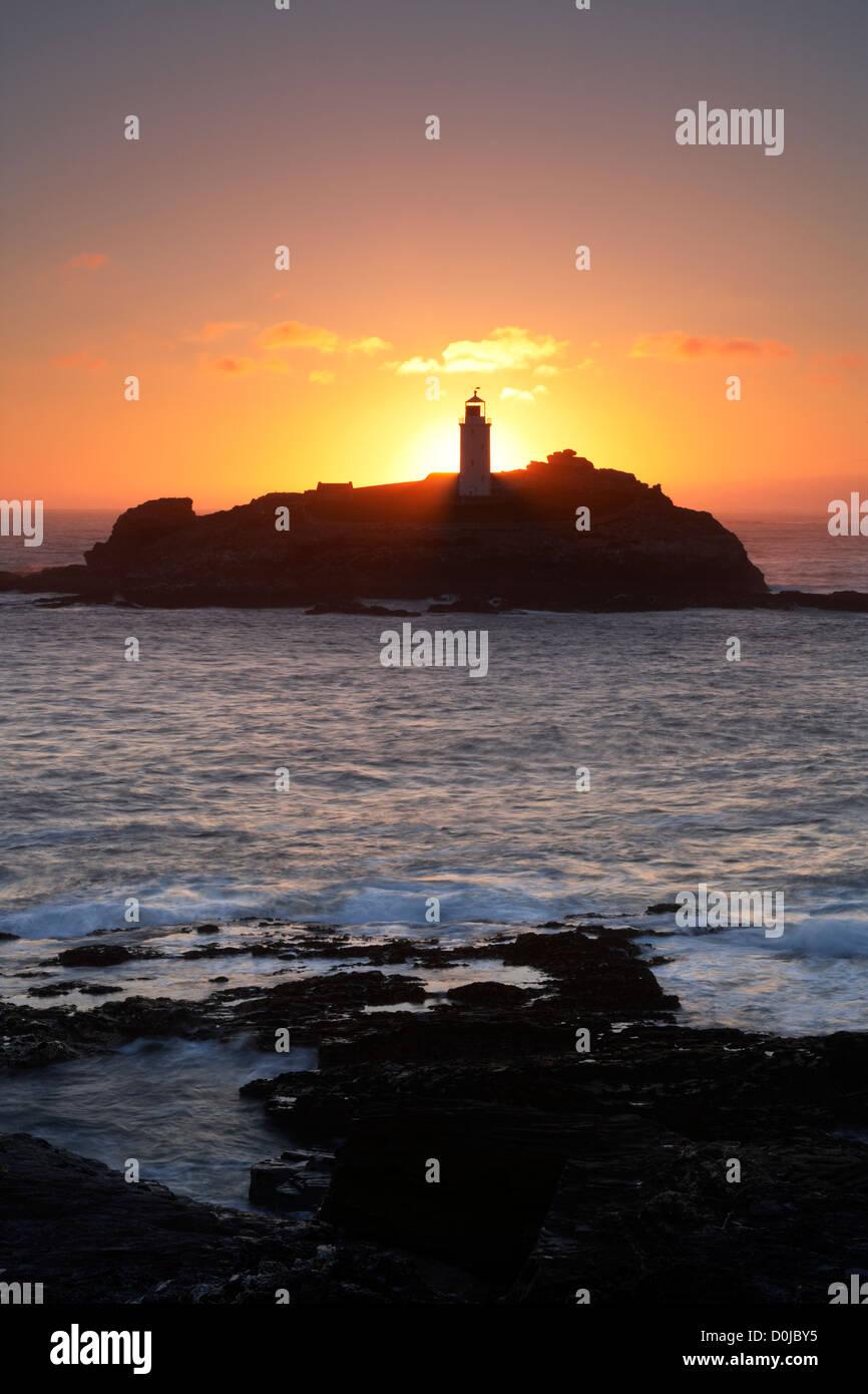 Sunset behind Godrevy Lighthouse on the Cornish coast. - Stock Image