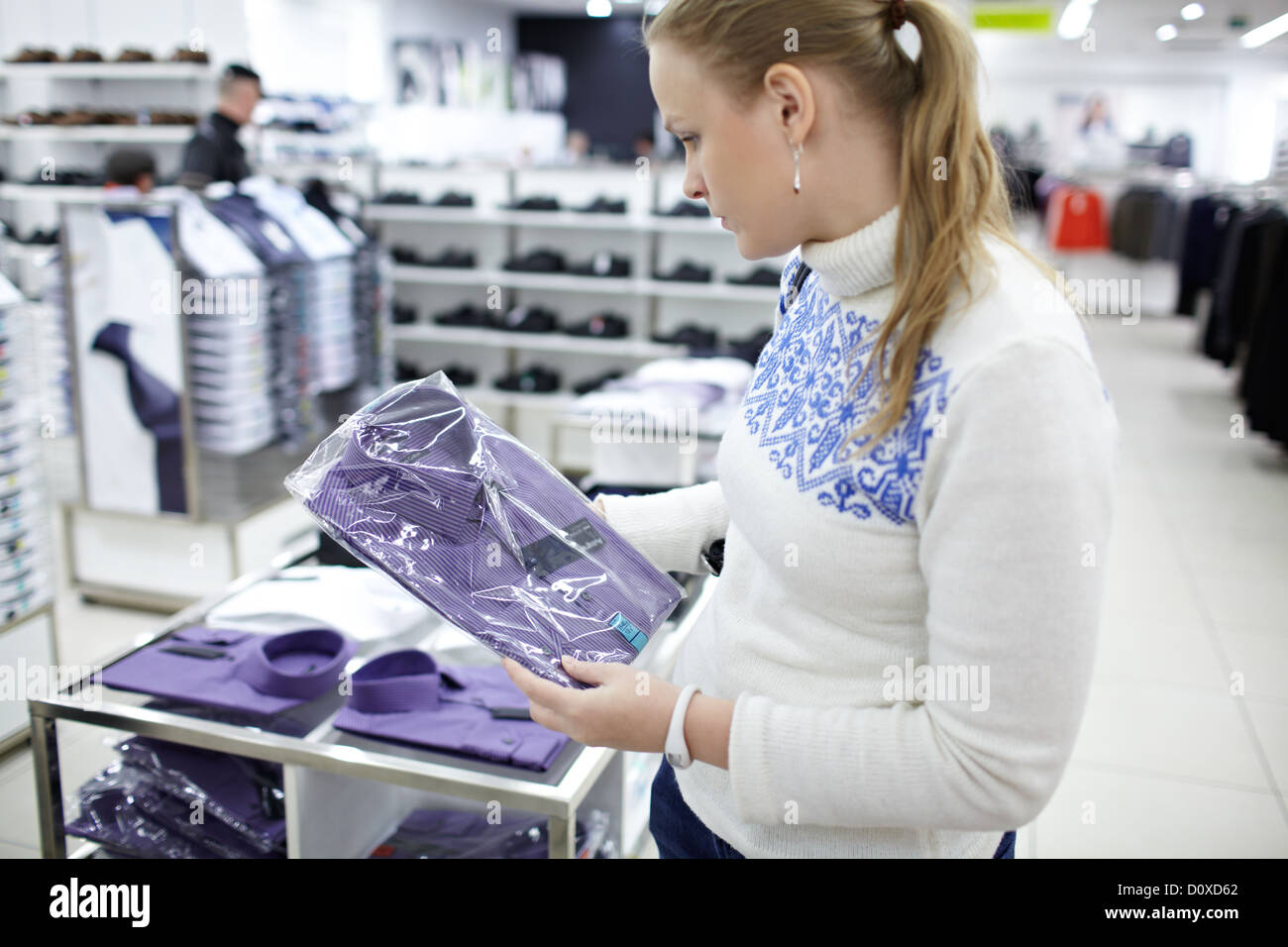 Woman with shirt in her hands. - Stock Image