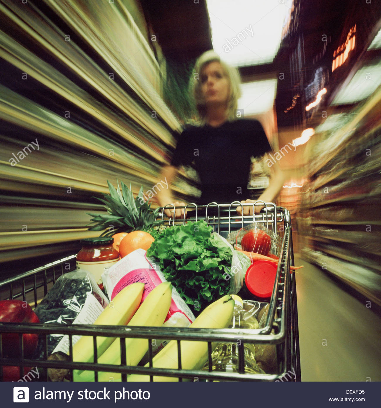 Woman in supermarket with trolley, motion blur - Stock Image