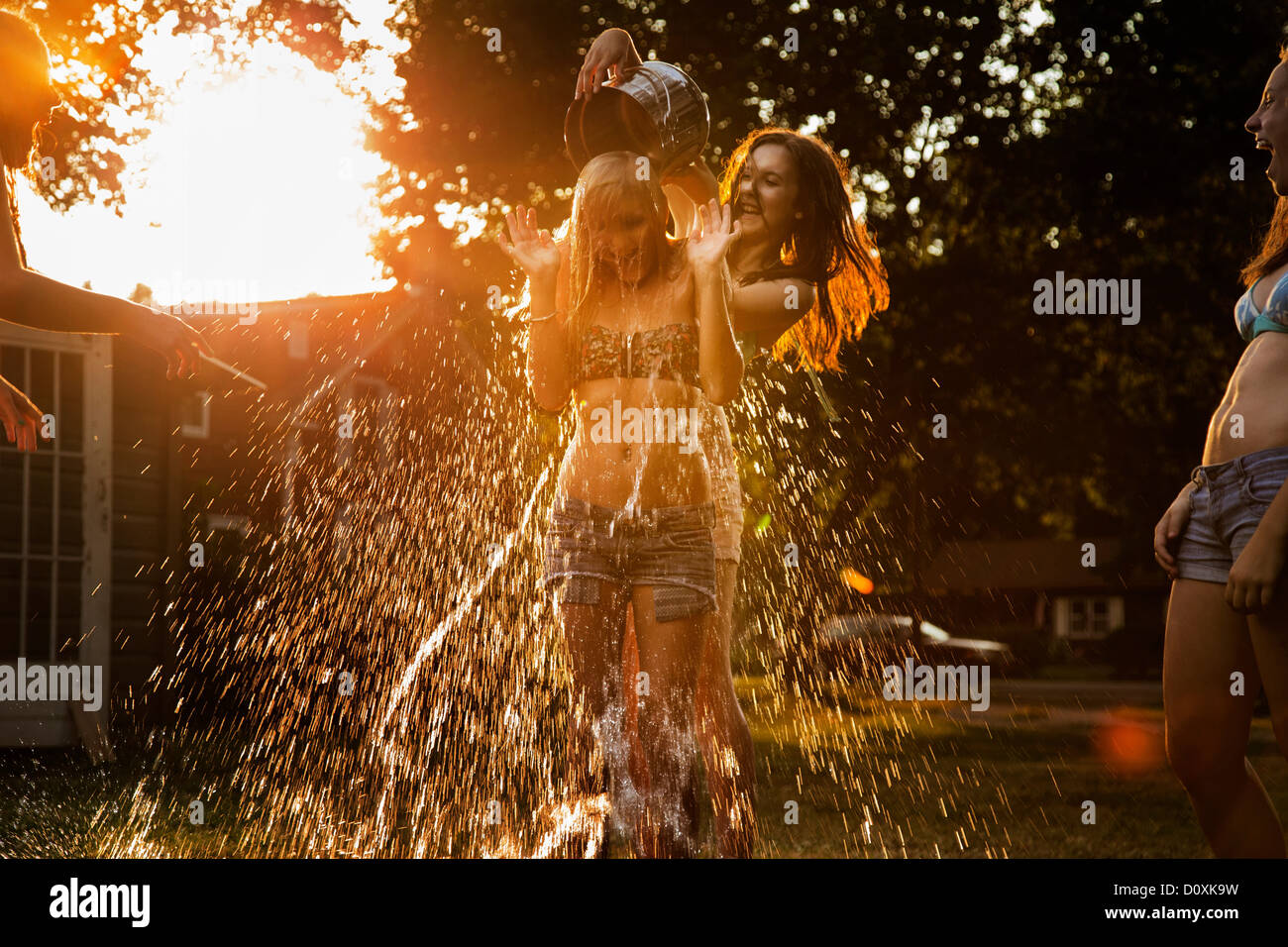 Girl pouring bucket of water over friend's head - Stock Image