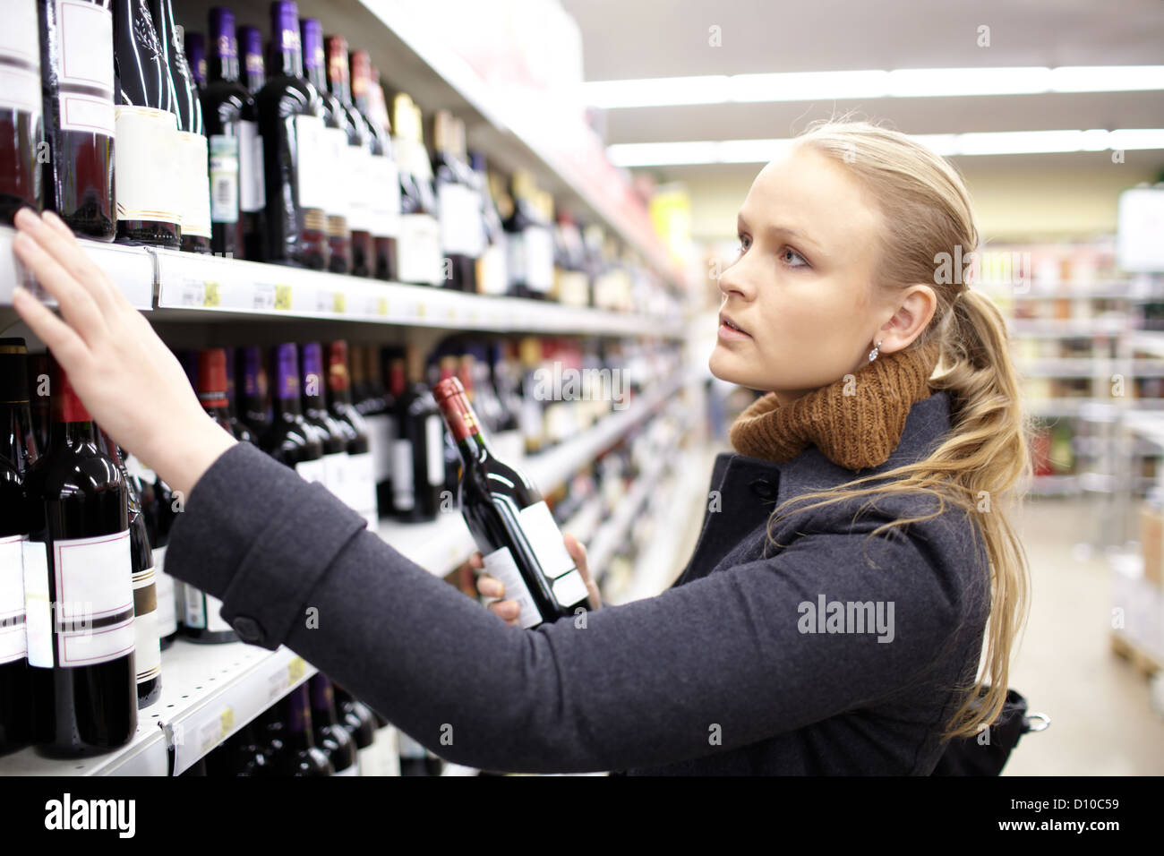 Young woman is choosing wine in the supermarket. - Stock Image