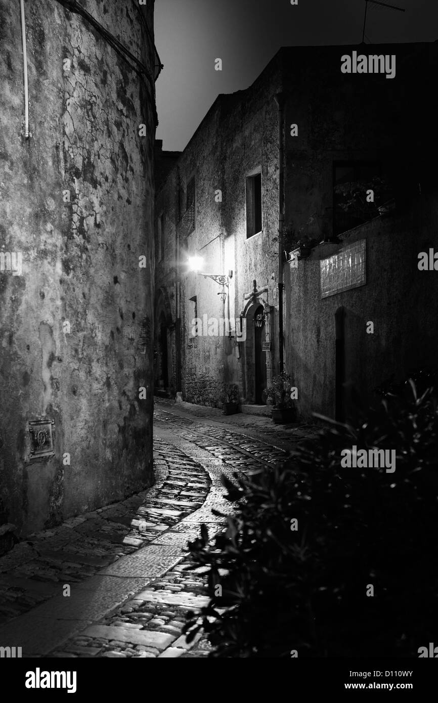 Curved cobblestone street between buildings in Sicily illuminated by street lights - Stock Image