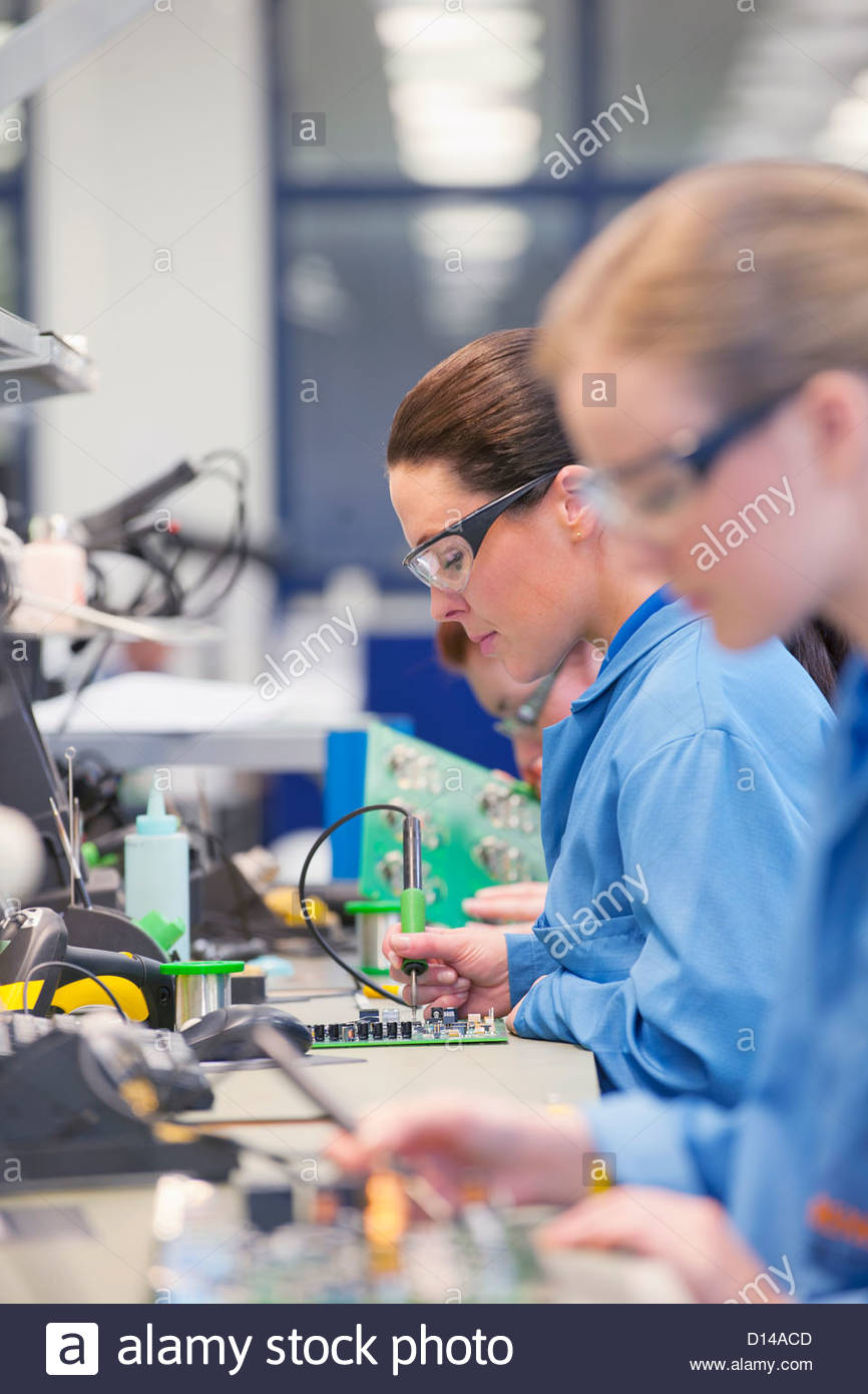 Technicians soldering circuit boards on production line in manufacturing plant - Stock Image